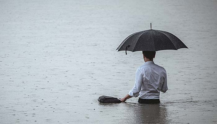 Man in flood water with umbrella from North Queensland Insurance Brokers Townsville